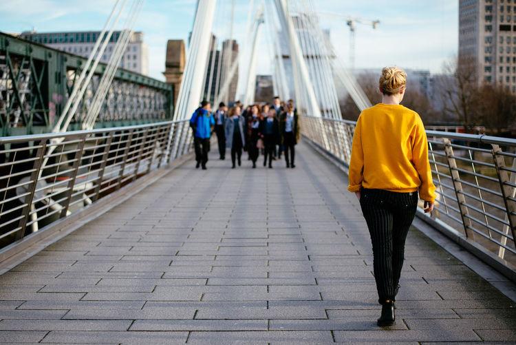 Full Length Rear View Of Woman Walking On Bridge In City