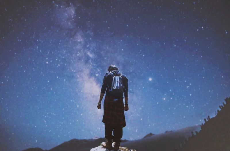 Rear view of man standing on rock against sky at night