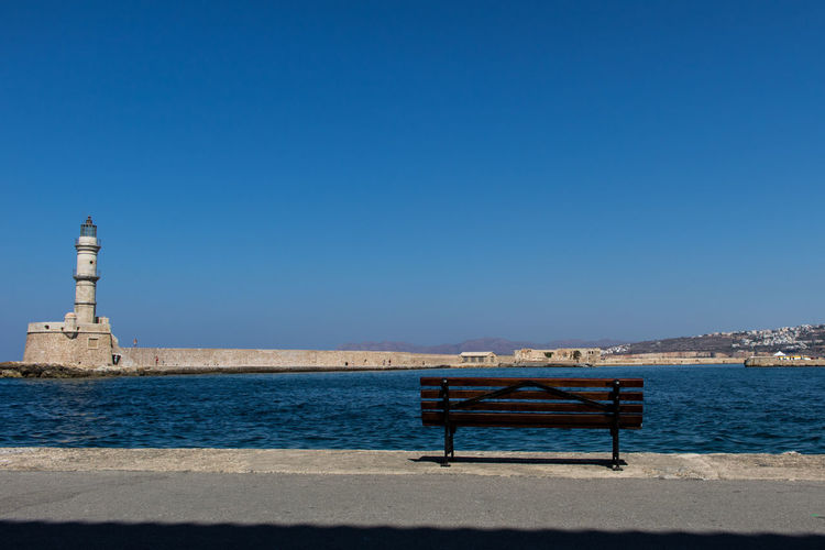 Bench On Promenade Against Clear Blue Sky