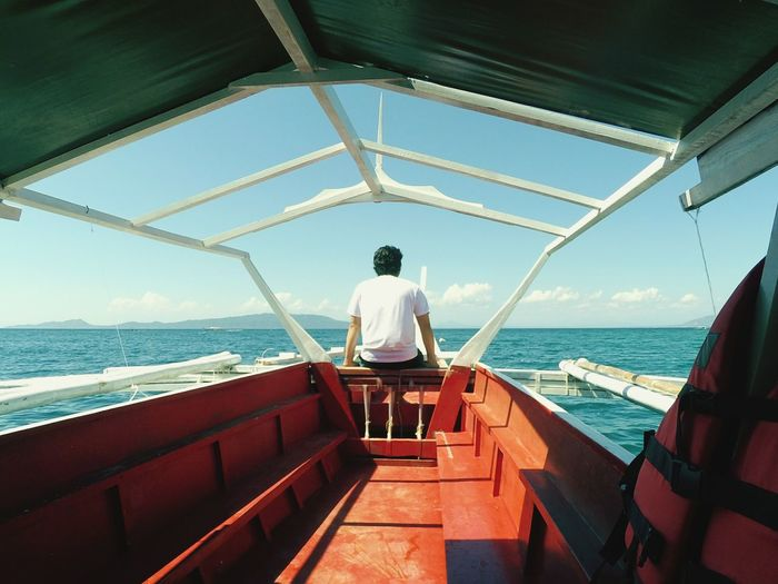 Rear View Of Man Sitting In Boat At Sea