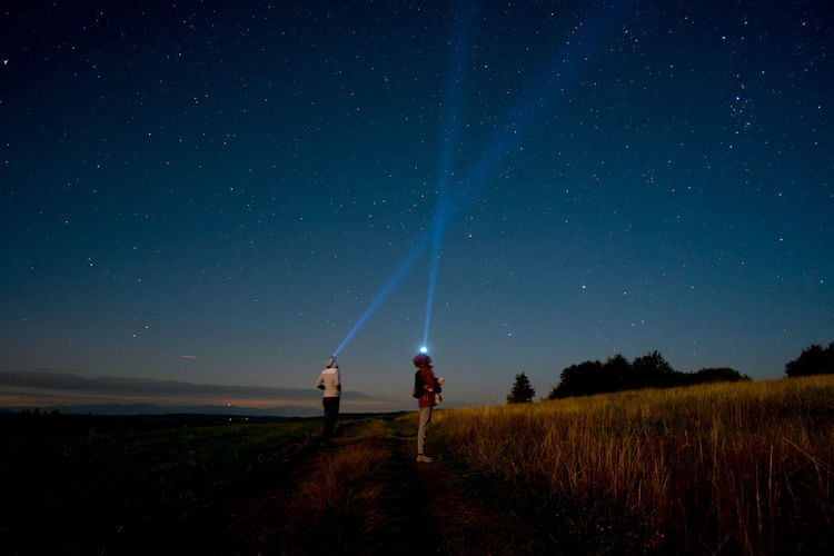 People with illuminated headlamps while standing on field against starry sky at night