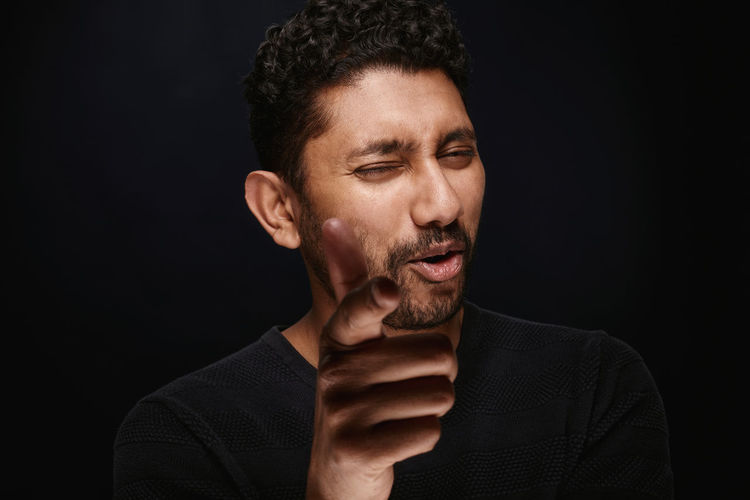 Close-Up Of Young Man Gesturing While Winking Against Black Background