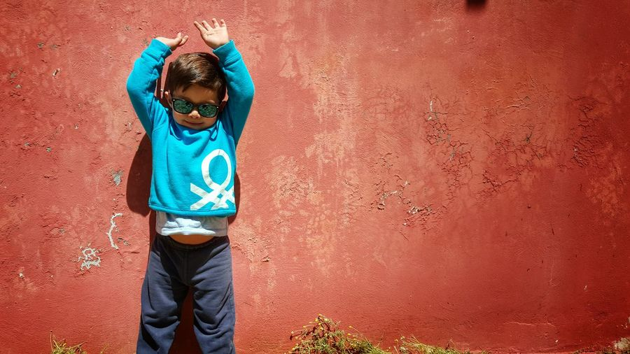 Happy Young Boy Against Red Wall