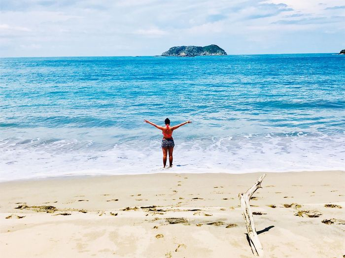 Rear view of woman with arms outstretched standing at beach