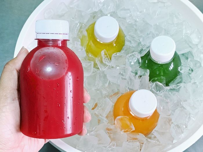 Hand holding the bottle of cold pressed fruit juice with ice bucket. Fresh Drink Vegetable Fruits Vitamin Colorful Detox Healthy Eating Cold Pressed Juice Juice Ice Container Bottle Close-up High Angle View Human Body Part Human Hand Food And Drink Healthy Eating Red