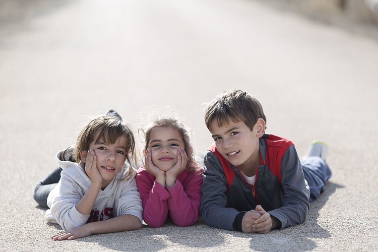 Three children lying on the floor one on top of the other. Horizontal shot with natural light Children Children's Portraits Spanish Tree Children Boys Caucasian Ethnicity Child Childhood Day Girls Happiness Leisure Activity Looking At Camera Looking At The Camera Outdoors People person Portrait Real People Smiling Togetherness