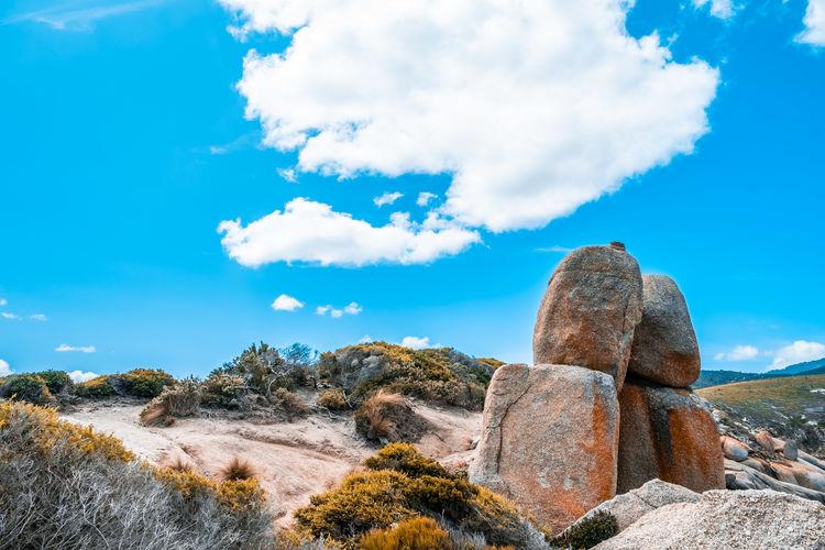 Large orange rocks and native australian shrubs against vivid blue sky and white clouds