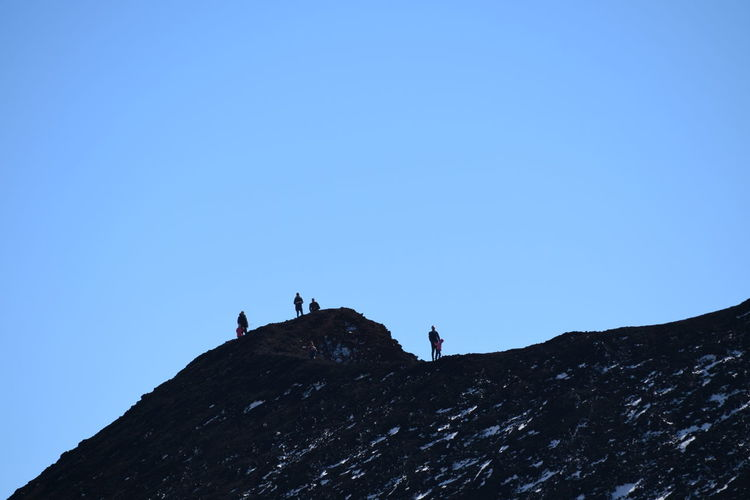 Low angle view of people on mountain against clear blue sky