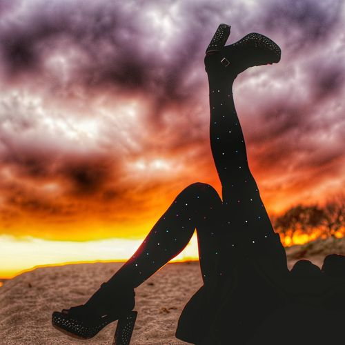 Silhouette woman sculpture against sea during sunset