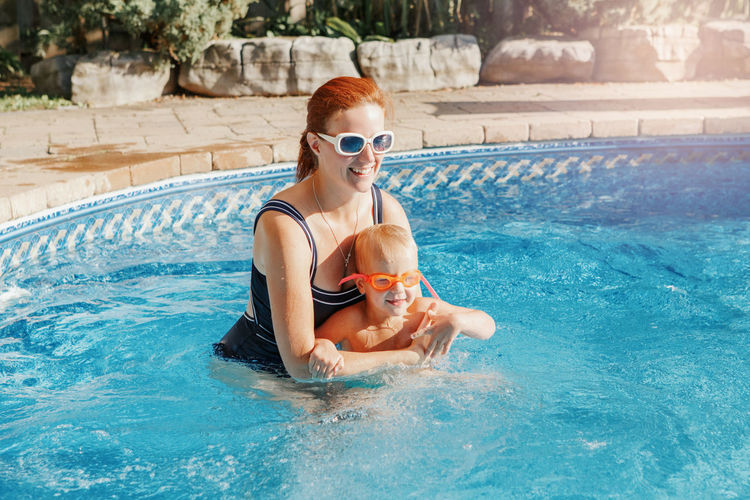Cheerful mother with son wearing glasses in swimming pool