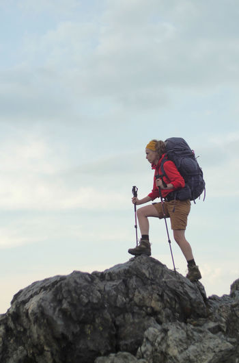 portrait of a caucasian female hiker standing on the rock with backpack Alpine Backpacking Boots Camping Expedition Freedom Hiking Nature Travel Trekking Woman Youth Activity Adventure Backpack Caucasian Climbing Cloud - Sky Day Female Full Length Girl Hobby Leisure Activity Lifestyles Men Mountain Nature One Person Outdoors People Real People Rock Rock - Object Rock Formation Sky Solid Standing Two People Walking