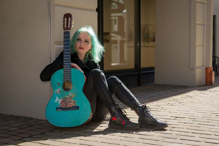 Hipster young woman with turquoise guitar in city