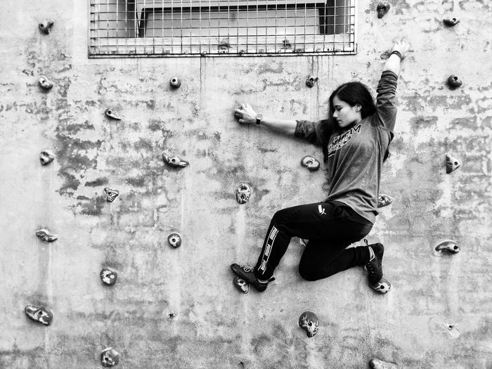 Side view of young woman against wall