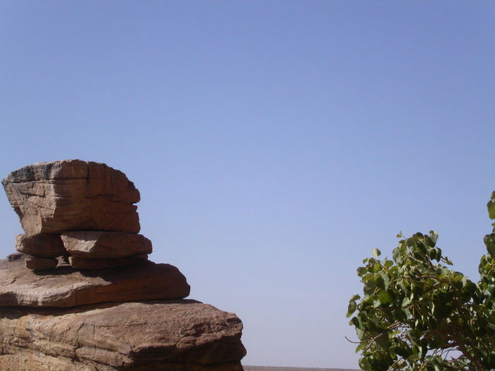 Heap of rocks with tree against clear sky