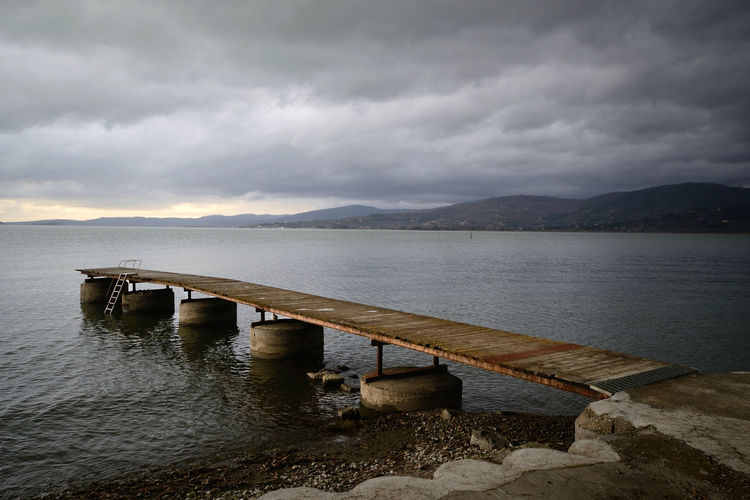 lake view with a jetty in foreground, on a cloudy winter day Trasimeno Umbria Lake View Water Real People Jetty Pier Concrete Wood Wooden Shore Cloud - Sky Cloud Winter Grey Sky Sunlight Nature No People Architecture Outdoors Tranquility Beauty In Nature Mountain