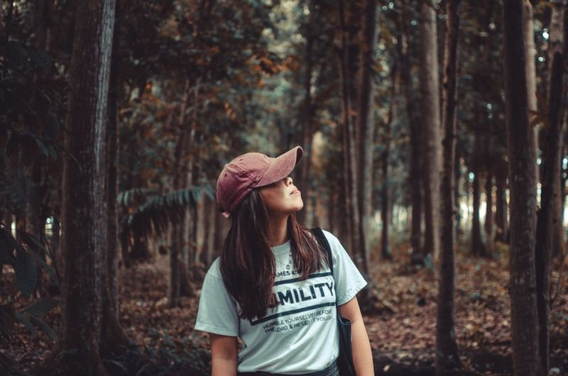 Full length of teenage girl standing in forest