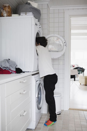 Side view of boy using washing machine at home