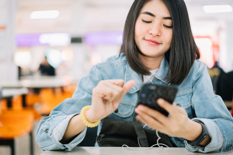 Mid adult woman looking at camera while sitting on mobile phone