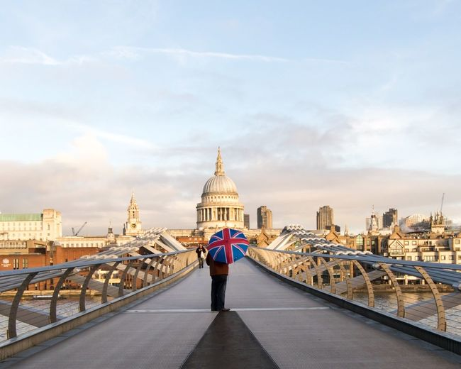Low section of man with umbrella on london millennium footbridge against sky in city
