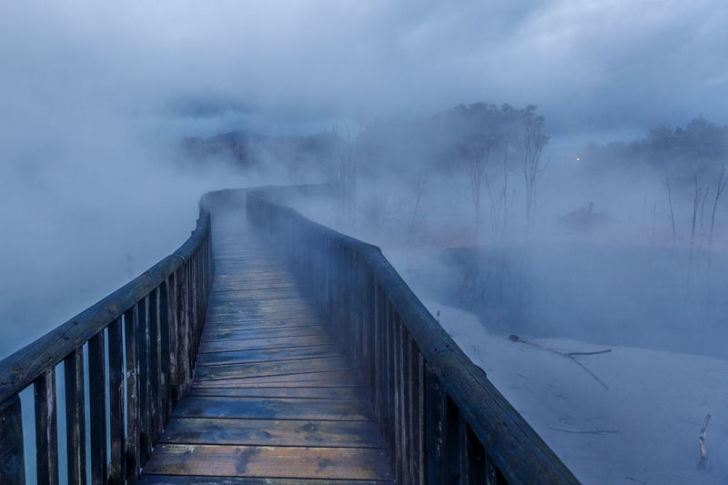 Wooden Footbridge Over Frozen Lake Against Sky During Foggy Weather