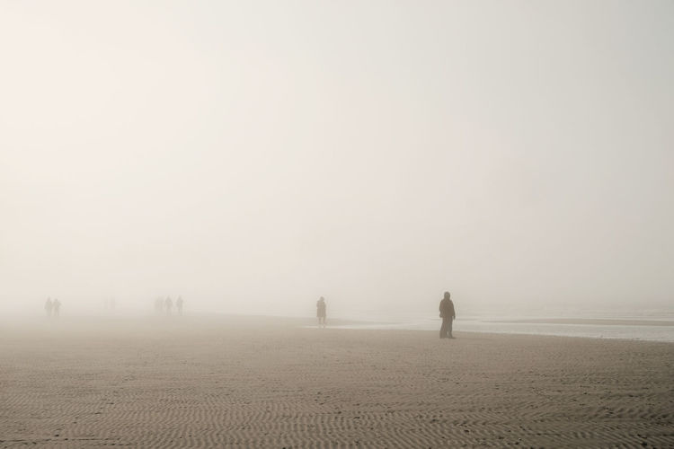 People on beach against sky during foggy weather