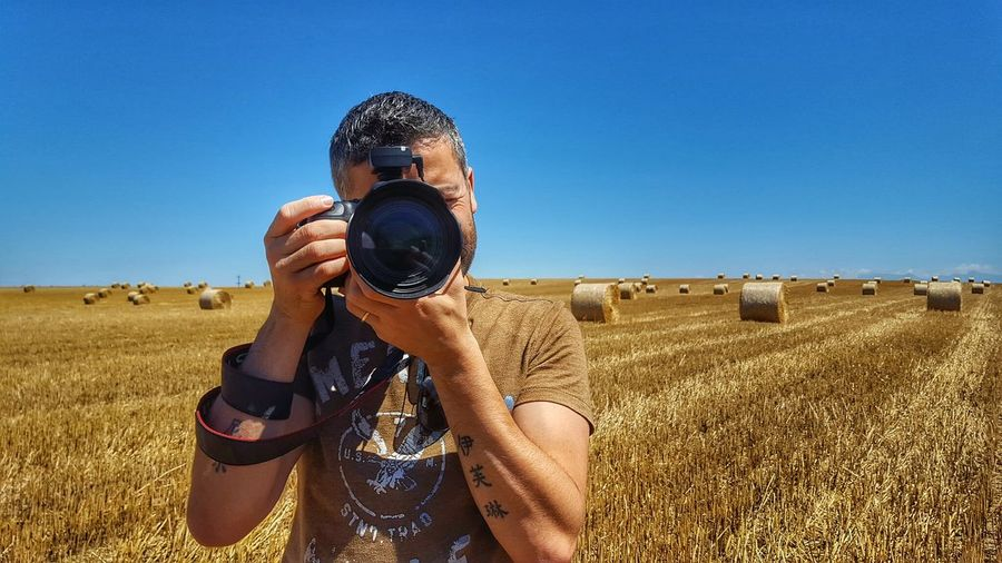Man photographing through digital camera against hay bales on field