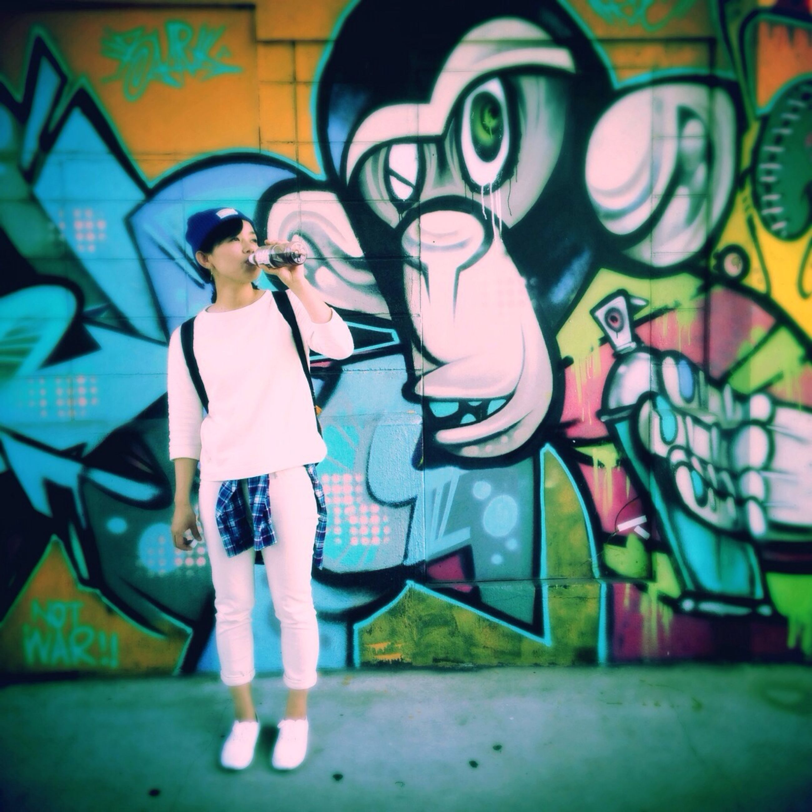 graffiti, art, creativity, lifestyles, art and craft, casual clothing, full length, wall - building feature, leisure activity, indoors, childhood, human representation, built structure, architecture, standing, person, multi colored, front view