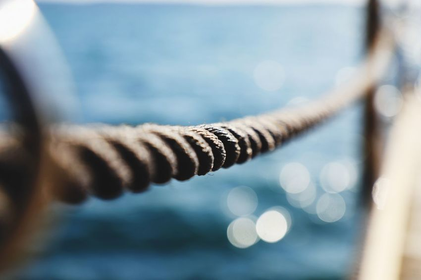 Everyone needs a bit of help Bokeh Beach Seaside_collection Seaside Help Rope Summer Close-up Focus On Foreground Selective Focus Day Nature No People Outdoors Water Sunlight Connection Drop Plant Purity Wood - Material Rusty Tranquility