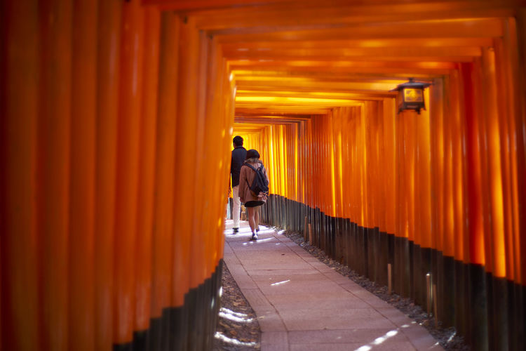 Rear View Of People Walking In Torii Gate