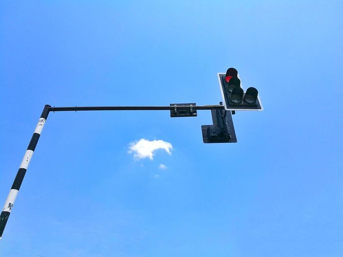 Low angle view of person against clear blue sky