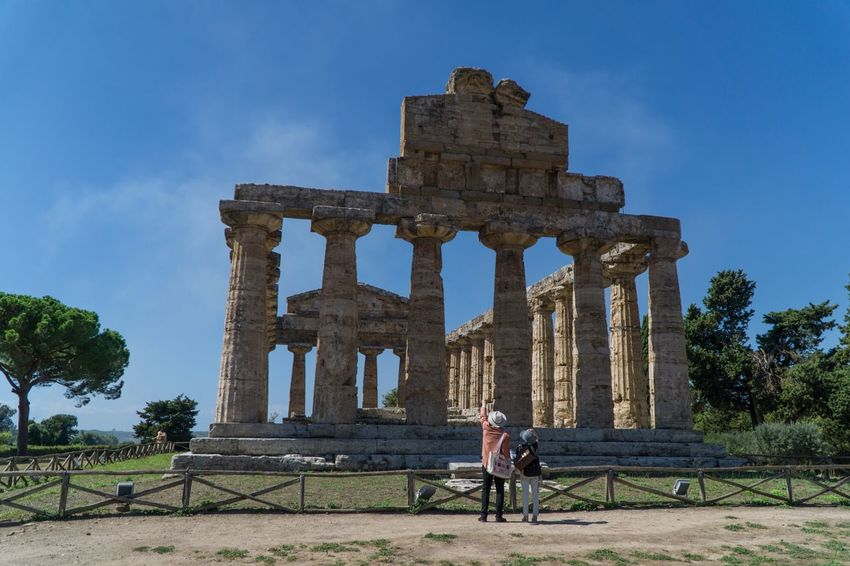 Paestum Roman ruins, Italy Temple Architecture The Past History Sky Built Structure Ancient Tree Ancient Civilization Real People Travel Plant Tourism Old Ruin Travel Destinations Nature Women Men Architectural Column Leisure Activity Adult The Traveler - 2018 EyeEm Awards