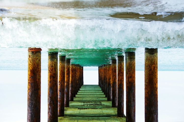 Rusted Columns Supporting Pier At Sea