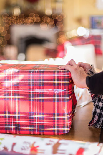 Cropped hands of woman wrapping gift at home