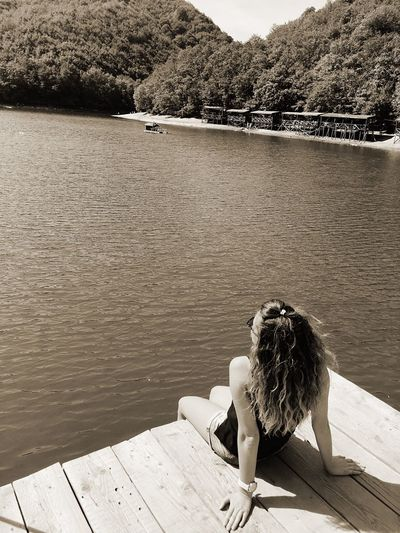 Young woman sitting on pier over lake