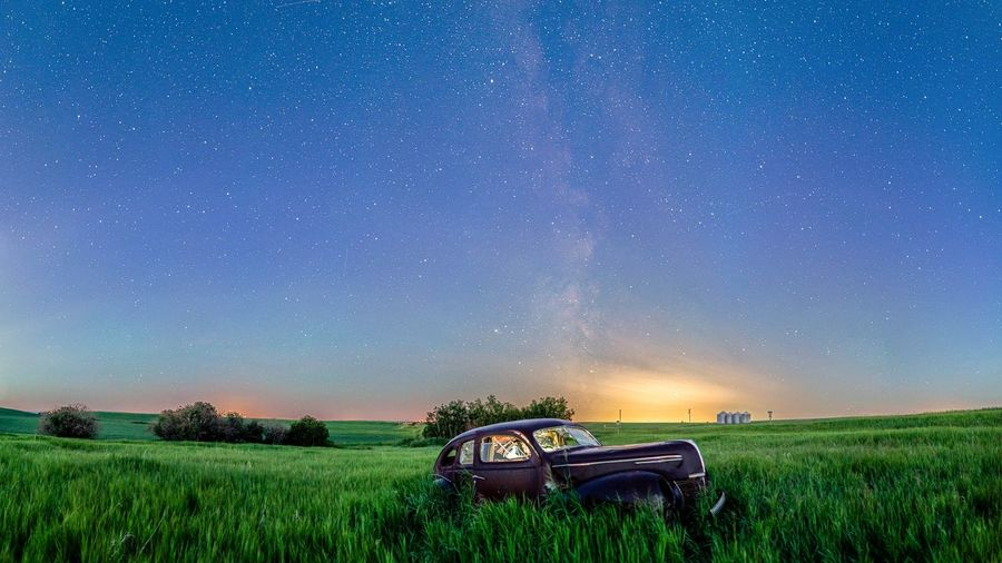 Tractor on field against sky at night