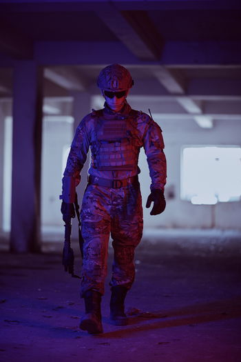 Full length of soldier walking in illuminated room