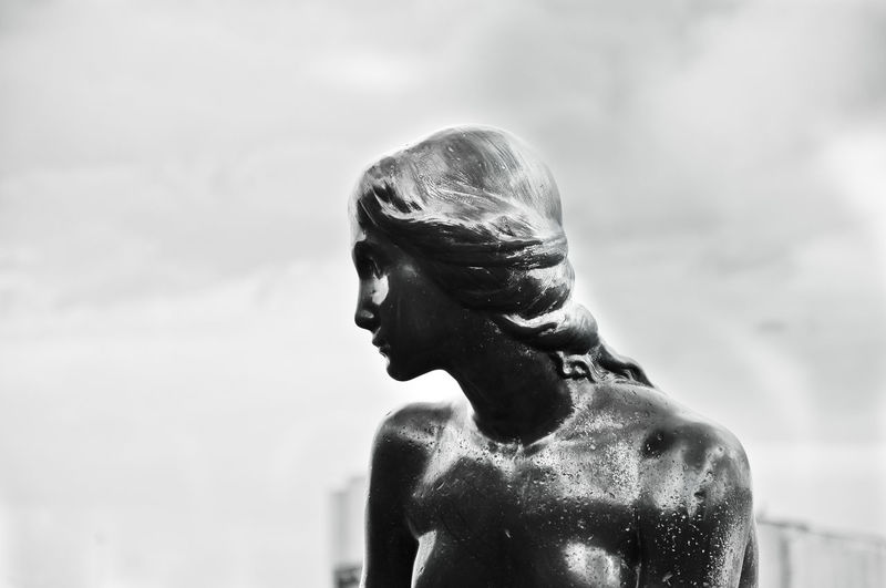 Close-up of old statue against sky