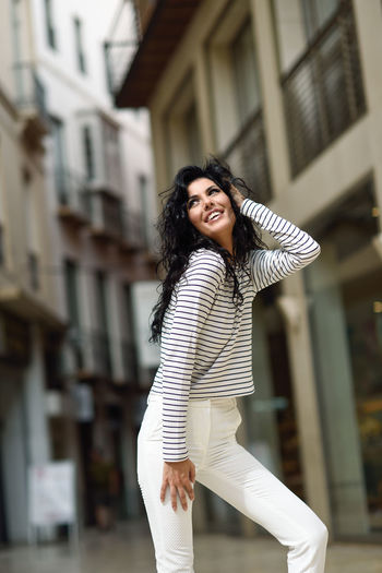Brunette woman, model of fashion, wearing casual white clothes smiling in the street. Young girl with curly hairstyle standing in urban background.