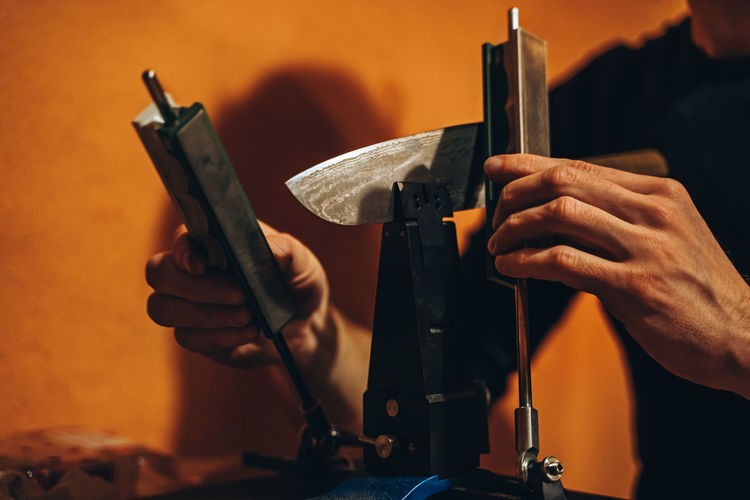 Cropped Hands Of Manual Worker Repairing Machinery In Workshop