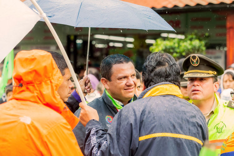 Banos De Agua Santa, Ecuador - 23 June ,2016: Mayor Of Banos De Agua Santa, Marlon Guevara Waiting For President Of Ecuador, Rafael Correa To Visit The City, Ecuador, South America Adult Adults Only BañosEcuador Bonding Chaos Day Elections2017 Manifestation Mature Adult Mayer Men News Only Men Outdoor Outdoors People People Watching Police President Rafael Correa Rain Smiling Togetherness Vacations Young Adult