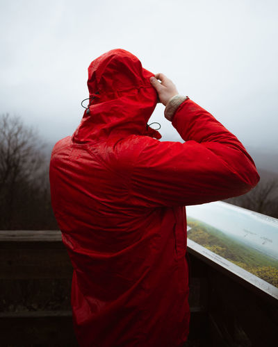 Rear view of man standing by red umbrella against sky