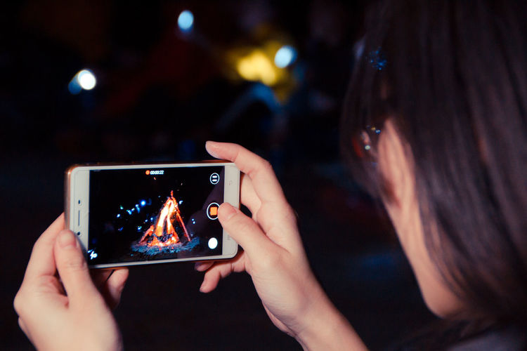 Cropped Image Of Woman Filming Bonfire Through Mobile Phone At Night