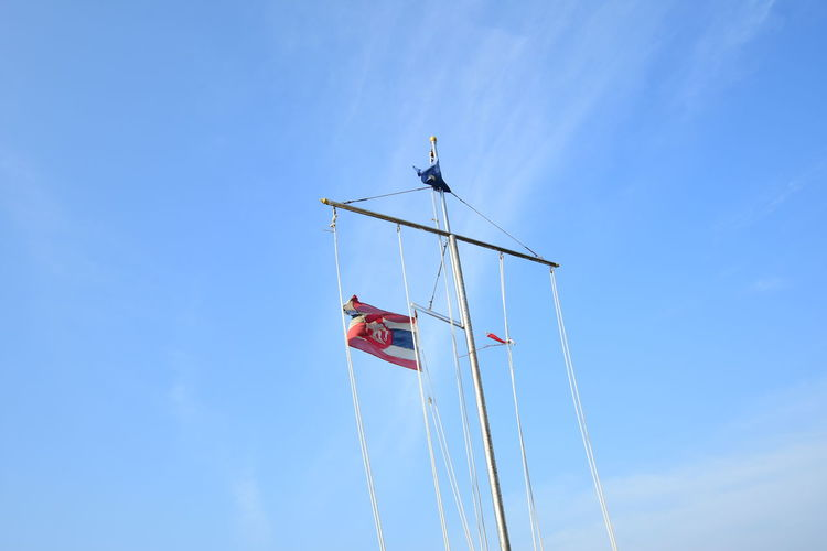 Low angle view of mast against blue sky