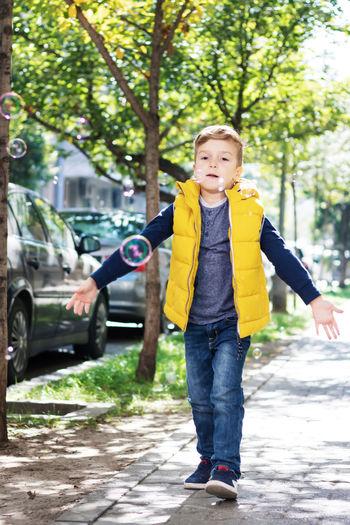 Portrait of boy standing on street in city