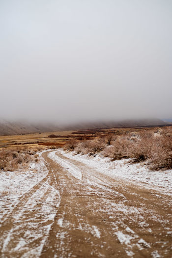 Sky Environment Landscape Road Scenics - Nature No People Non-urban Scene Nature Outdoors Dirt Road Desert Snow Tire Tracks In Snow Misty Morning Cloudy Day Wintertime Sierra Nevada Mountains Valleys Desert Valley Snow Covered Snow Day California Cold Weather Tire Tracks Off Road Rural America