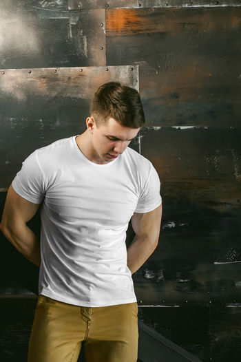 Muscular man standing by wall