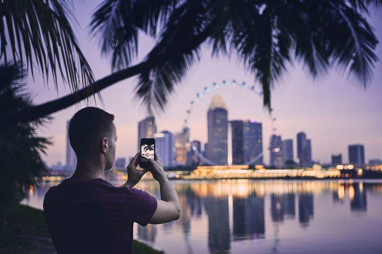Man photographing by cityscape against sky during sunset