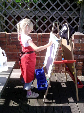 Art Easel Art. Blue Board Brick Wall Casual Clothing Child Child Painting Childhood Day Drawing Drawing Board Easel Fence Full Length Girl. Leisure Activity Outdoors Red Side View Small Girl. Standing Summer Summer Activity Water