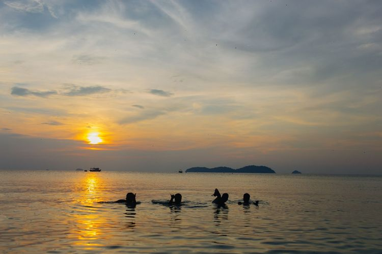 Silhouette People Swimming In Sea Against Sky During Sunset