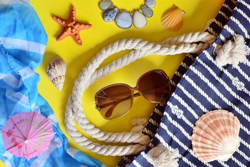 Directly above shot of seashells and personal accessories on table